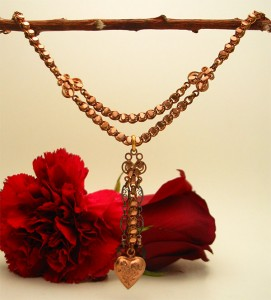 The heart drop necklace is made with antique rose gold-filled chain and charm, garnets and antiqued sterling findings. $160